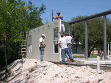 Workers install fiber cement structural insulated wall panels, which consist of two sheet of 5/16th-inch cement board laminated to 4-inch polystyrene foam.